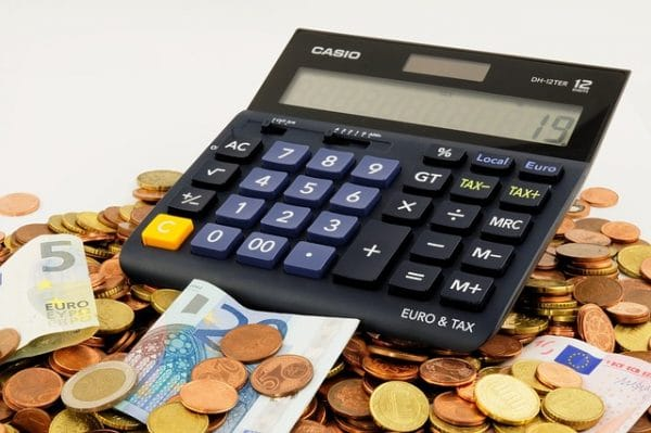 Calculadora junto a billetes y monedas tirados en una mesa para calcular el precio de un trastero