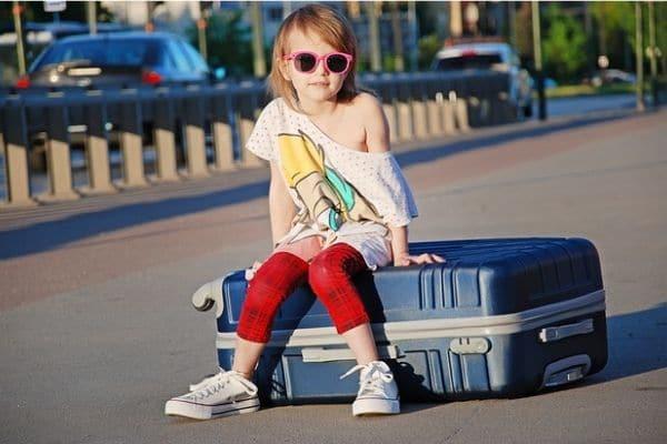 Niña sentada encima de una maleta en la calle